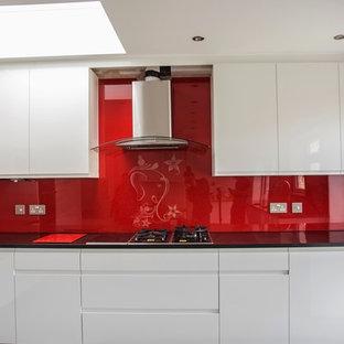 Modern kitchen appliance - Minimalist kitchen photo in Hertfordshire with red backsplash and glass sheet backsplash