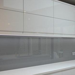 Ispirazione per una cucina minimalista con paraspruzzi grigio e paraspruzzi con lastra di vetro