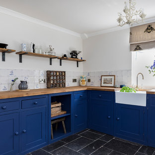 Inspiration for a large country l-shaped eat-in kitchen in London with a farmhouse sink, shaker cabinets, blue cabinets, wood benchtops, white splashback, ceramic splashback, panelled appliances, limestone floors, no island and blue floor.