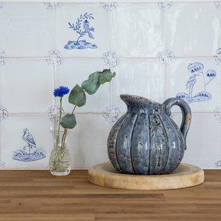 Идея дизайна: большая угловая кухня в стиле кантри с обеденным столом, раковиной в стиле кантри, фасадами в стиле шейкер, синими фасадами, деревянной столешницей, белым фартуком, фартуком из керамической плитки, техникой под мебельный фасад, полом из известняка и синим полом без острова