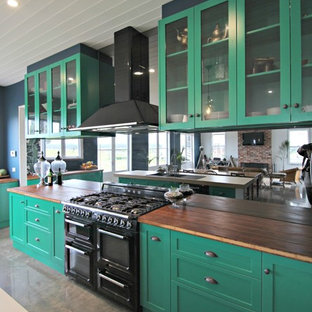 This is an example of a large eclectic l-shaped eat-in kitchen in Melbourne with a farmhouse sink, shaker cabinets, green cabinets, wood benchtops, metallic splashback, mirror splashback, black appliances, concrete floors and with island.