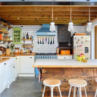 Offene, Mittelgroße Stilmix Küche in L-Form mit Landhausspüle, Schrankfronten im Shaker-Stil, weißen Schränken, Arbeitsplatte aus Holz, Küchenrückwand in Weiß, bunten Elektrogeräten, Betonboden, Kücheninsel und Rückwand aus Metrofliesen in London
