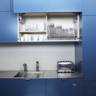 Imagen de cocina comedor en U, actual, pequeña, con fregadero integrado, armarios con paneles lisos, puertas de armario azules, encimera de acero inoxidable, salpicadero blanco, salpicadero de vidrio templado, electrodomésticos de acero inoxidable y suelo de baldosas de porcelana