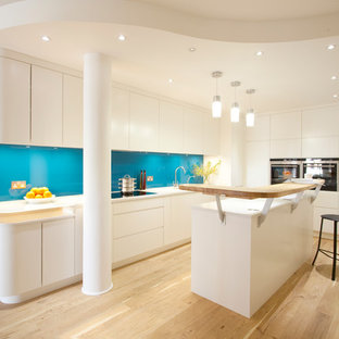 Inspiration for a mid-sized scandinavian l-shaped kitchen in London with flat-panel cabinets, white cabinets, glass benchtops, blue splashback, glass sheet splashback, light hardwood floors and with island.