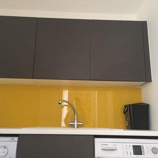 バッキンガムシャーの中くらいのコンテンポラリースタイルのおしゃれなキッチン (一体型シンク、フラットパネル扉のキャビネット、珪岩カウンター、ミラータイルのキッチンパネル、パネルと同色の調理設備、クッションフロア) の写真