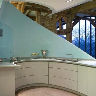 Cette image montre une grand cuisine ouverte design avec un évier encastré, un placard à porte plane, des portes de placard bleues, un plan de travail en surface solide, un électroménager blanc et une péninsule.