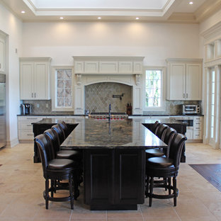 Design ideas for an expansive traditional l-shaped open plan kitchen in New York with a farmhouse sink, granite benchtops, beige splashback, glass tile splashback, stainless steel appliances, with island, recessed-panel cabinets, white cabinets, ceramic floors and beige floor.