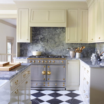 Country kitchen photo in New York with a farmhouse sink, shaker cabinets, yellow cabinets, gray backsplash, stainless steel appliances and an island