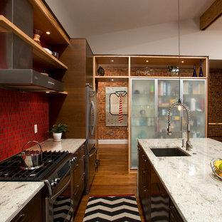 Esempio di una cucina contemporanea di medie dimensioni con lavello a vasca singola, ante lisce, ante marroni, top in granito, paraspruzzi rosso, paraspruzzi in gres porcellanato, elettrodomestici in acciaio inossidabile, pavimento in legno massello medio e isola