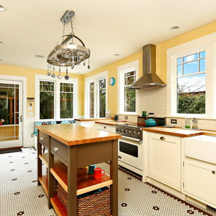 This is an example of a mid-sized traditional galley separate kitchen in Seattle with a farmhouse sink, recessed-panel cabinets, white cabinets, wood benchtops, white splashback, subway tile splashback, stainless steel appliances, ceramic floors, with island, yellow floor and brown benchtop.
