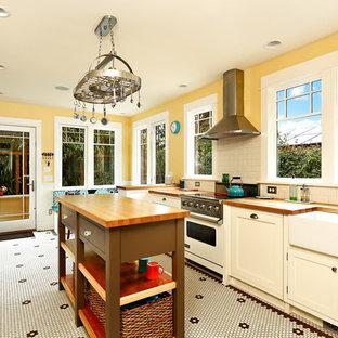 Неиссякаемый источник вдохновения для домашнего уюта: отдельная, параллельная кухня среднего размера в викторианском стиле с раковиной в стиле кантри, фасадами с утопленной филенкой, белыми фасадами, деревянной столешницей, белым фартуком, фартуком из плитки кабанчик, техникой из нержавеющей стали, полом из керамической плитки, островом, желтым полом и коричневой столешницей