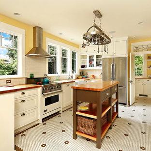 シアトルの中サイズのヴィクトリアン調のおしゃれなキッチン (エプロンフロントシンク、シェーカースタイル扉のキャビネット、白いキャビネット、木材カウンター、白いキッチンパネル、サブウェイタイルのキッチンパネル、シルバーの調理設備の、マルチカラーの床、セラミックタイルの床、茶色いキッチンカウンター) の写真