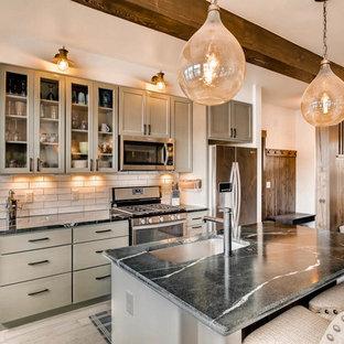 デンバーの小さいラスティックスタイルのおしゃれなキッチン (シングルシンク、シェーカースタイル扉のキャビネット、緑のキャビネット、ソープストーンカウンター、白いキッチンパネル、磁器タイルのキッチンパネル、シルバーの調理設備、磁器タイルの床、白い床) の写真