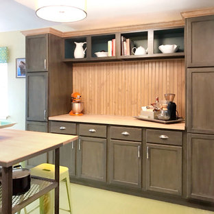 This is an example of a mid-sized transitional kitchen in Columbus with a drop-in sink, recessed-panel cabinets, dark wood cabinets, granite benchtops, green splashback, black appliances, painted wood floors, with island, green floor and green benchtop.