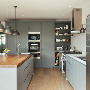 Design ideas for a transitional l-shaped eat-in kitchen in London with an integrated sink, shaker cabinets, grey cabinets, wood benchtops, stainless steel appliances, light hardwood floors, with island, beige floor and brown benchtop.