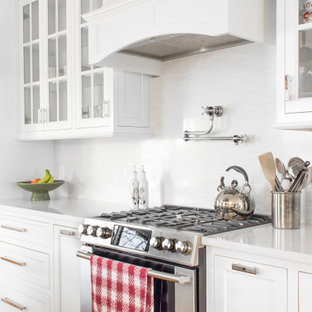 Large coastal eat-in kitchen designs - Eat-in kitchen - large coastal galley medium tone wood floor and brown floor eat-in kitchen idea in Providence with an undermount sink, flat-panel cabinets, white cabinets, quartz countertops, white backsplash, quartz backsplash, stainless steel appliances, an island and white countertops