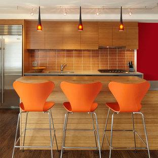 Modelo de cocina contemporánea con encimera de cuarzo compacto, electrodomésticos de acero inoxidable, armarios con paneles lisos, salpicadero naranja y salpicadero de azulejos de vidrio