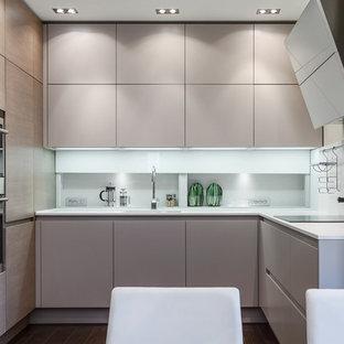 Esempio di una cucina contemporanea con ante lisce, ante beige, elettrodomestici in acciaio inossidabile, top in superficie solida e paraspruzzi bianco