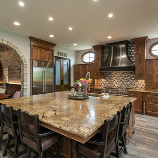 This is an example of a large traditional u-shaped eat-in kitchen in Detroit with an undermount sink, recessed-panel cabinets, stainless steel appliances, with island, grey floor, beige benchtop, dark wood cabinets, granite benchtops, multi-coloured splashback, mosaic tile splashback and dark hardwood floors.