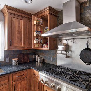 Photo of a mid-sized industrial l-shaped eat-in kitchen in New York with an undermount sink, beaded inset cabinets, medium wood cabinets, granite benchtops, grey splashback, slate splashback, stainless steel appliances, ceramic floors, with island and brown floor.