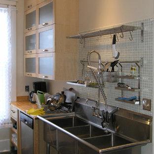 Moderne Küche mit Triple-Waschtisch, hellen Holzschränken, Küchenrückwand in Grün, Rückwand aus Glasfliesen und Küchengeräten aus Edelstahl in Jacksonville