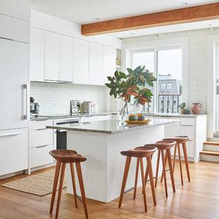ボストンのコンテンポラリースタイルのおしゃれなキッチン (アンダーカウンターシンク、フラットパネル扉のキャビネット、白いキャビネット、白いキッチンパネル、レンガのキッチンパネル、パネルと同色の調理設備、無垢フローリング、茶色い床、グレーのキッチンカウンター) の写真