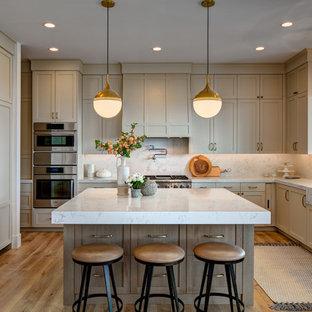 Immagine di una grande cucina classica con ante con riquadro incassato, top in marmo, paraspruzzi in marmo, elettrodomestici in acciaio inossidabile, lavello sottopiano, ante beige, paraspruzzi bianco, pavimento in legno massello medio, pavimento marrone e top bianco