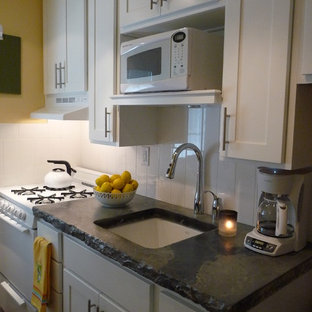 Design ideas for a small transitional single-wall separate kitchen in St Louis with a single-bowl sink, shaker cabinets, white cabinets, concrete benchtops, white splashback, subway tile splashback, white appliances, medium hardwood floors and no island.
