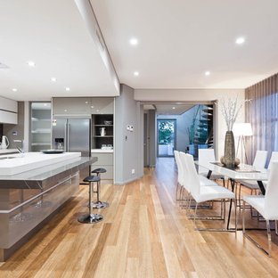 This is an example of a contemporary eat-in kitchen in Perth with a double-bowl sink, flat-panel cabinets, grey cabinets, grey splashback, stainless steel appliances, light hardwood floors, with island and beige floor.