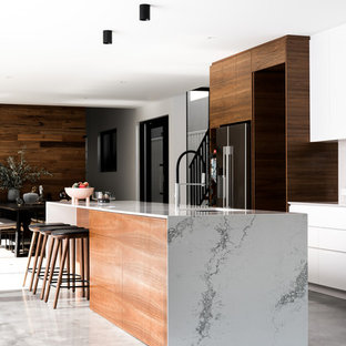 Inspiration for a large contemporary galley open plan kitchen in Perth with an undermount sink, flat-panel cabinets, white cabinets, quartz benchtops, white splashback, stone slab splashback, black appliances, concrete floors, with island and grey floor.
