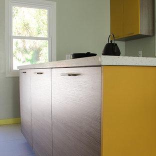 ロサンゼルスの小さいコンテンポラリースタイルのおしゃれなキッチン (ドロップインシンク、フラットパネル扉のキャビネット、中間色木目調キャビネット、クオーツストーンカウンター、白いキッチンパネル、シルバーの調理設備) の写真