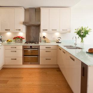 Kleine Moderne Küche in U-Form mit Doppelwaschbecken, flächenbündigen Schrankfronten, weißen Schränken, Glas-Arbeitsplatte, Küchengeräten aus Edelstahl, braunem Holzboden, Halbinsel und türkiser Arbeitsplatte in London