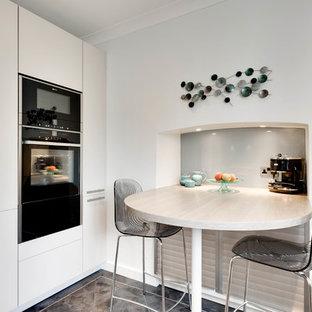 グロスタシャーの小さいコンテンポラリースタイルのおしゃれなキッチン (一体型シンク、フラットパネル扉のキャビネット、ベージュのキャビネット、珪岩カウンター、青いキッチンパネル、ガラス板のキッチンパネル、黒い調理設備、クッションフロア) の写真