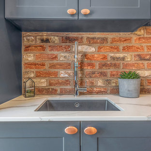 バークシャーのインダストリアルスタイルのおしゃれなキッチン (シェーカースタイル扉のキャビネット、青いキャビネット、レンガのキッチンパネル、黒い調理設備、茶色い床) の写真