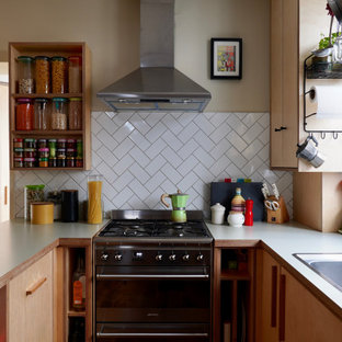 Small scandi l-shaped kitchen in Sussex with flat-panel cabinets, laminate countertops, white splashback, ceramic splashback, stainless steel appliances and white worktops.