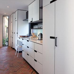 Modelo de cocina de galera, minimalista, con despensa, fregadero encastrado, armarios con paneles lisos, puertas de armario blancas, encimera de granito, salpicadero blanco, salpicadero de vidrio templado, electrodomésticos negros, suelo de ladrillo y una isla