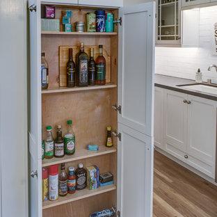 サンフランシスコの小さいコンテンポラリースタイルのおしゃれなキッチン (アンダーカウンターシンク、シェーカースタイル扉のキャビネット、白いキャビネット、茶色いキッチンパネル、セラミックタイルのキッチンパネル、シルバーの調理設備の、淡色無垢フローリング、アイランドなし) の写真