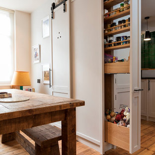 Inspiration for a small contemporary l-shaped kitchen pantry in London with a single-bowl sink, flat-panel cabinets, beige cabinets, granite worktops, green splashback, ceramic splashback, stainless steel appliances, light hardwood flooring, no island, brown floors and black worktops.