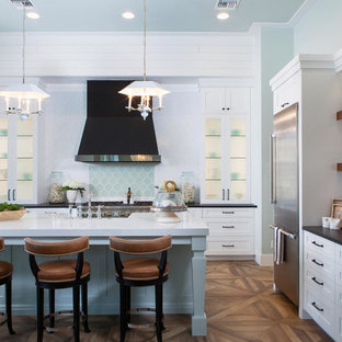 Large coastal open concept kitchen remodeling - Example of a large beach style l-shaped medium tone wood floor and brown floor open concept kitchen design in Miami with a farmhouse sink, shaker cabinets, white cabinets, marble countertops, multicolored backsplash, mosaic tile backsplash, stainless steel appliances and an island
