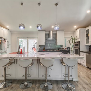 Example of a transitional u-shaped light wood floor and beige floor kitchen design in Los Angeles with an undermount sink, shaker cabinets, white cabinets, gray backsplash, glass tile backsplash, stainless steel appliances, an island and gray countertops