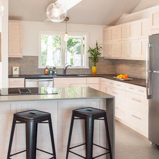 Réalisation d'une cuisine ouverte design en L de taille moyenne avec un placard à porte shaker, des portes de placard en bois clair, une crédence grise, une crédence en carreau briquette, un électroménager en acier inoxydable, un évier encastré, un plan de travail en verre recyclé, un îlot central et un sol gris.