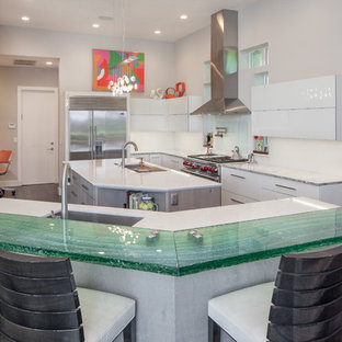 Contemporary enclosed kitchen designs - Example of a trendy u-shaped dark wood floor enclosed kitchen design in Miami with an undermount sink, flat-panel cabinets, white cabinets, glass countertops, white backsplash, stainless steel appliances, two islands and turquoise countertops