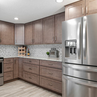 Design ideas for a mid-sized beach style u-shaped kitchen pantry in Tampa with an undermount sink, shaker cabinets, brown cabinets, granite benchtops, beige splashback, glass tile splashback, stainless steel appliances, ceramic floors, no island, beige floor and beige benchtop.