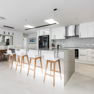 Photo of a large contemporary galley eat-in kitchen in Gold Coast - Tweed with an undermount sink, white cabinets, quartz benchtops, grey splashback, marble splashback, black appliances, ceramic floors, with island, beige floor, grey benchtop and flat-panel cabinets.
