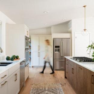 Ejemplo de cocina lineal, contemporánea, grande, abierta, con fregadero de doble seno, armarios estilo shaker, puertas de armario grises, encimera de cuarzo compacto, salpicadero blanco, electrodomésticos de acero inoxidable, suelo de madera clara, una isla, suelo amarillo y encimeras blancas