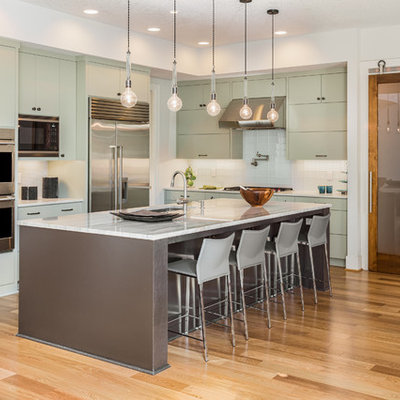Eat-in kitchen - contemporary l-shaped medium tone wood floor and brown floor eat-in kitchen idea in Los Angeles with an undermount sink, flat-panel cabinets, green cabinets, white backsplash, glass tile backsplash, stainless steel appliances and an island