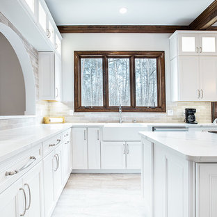 Photo of a large modern u-shaped eat-in kitchen in DC Metro with a farmhouse sink, raised-panel cabinets, white cabinets, quartz benchtops, beige splashback, travertine splashback, stainless steel appliances, porcelain floors, multiple islands, beige floor and white benchtop.
