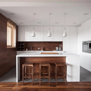 Mid-sized modern l-shaped kitchen in Los Angeles with flat-panel cabinets, white cabinets, timber splashback, stainless steel appliances, with island, an undermount sink, quartz benchtops, brown splashback, grey floor and white benchtop.