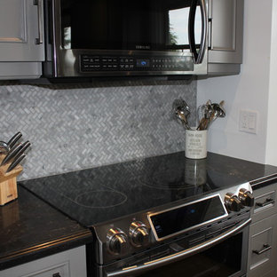 This is an example of a mid-sized transitional l-shaped open plan kitchen in Toronto with beaded inset cabinets, grey cabinets, mosaic tile splashback, black appliances, vinyl floors, with island, an undermount sink, grey splashback, beige floor and black benchtop.