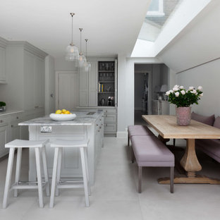 This is an example of a large classic l-shaped kitchen/diner in London with marble worktops, white splashback, limestone splashback, white appliances, an island, white worktops, a submerged sink, beaded cabinets, grey cabinets and grey floors.